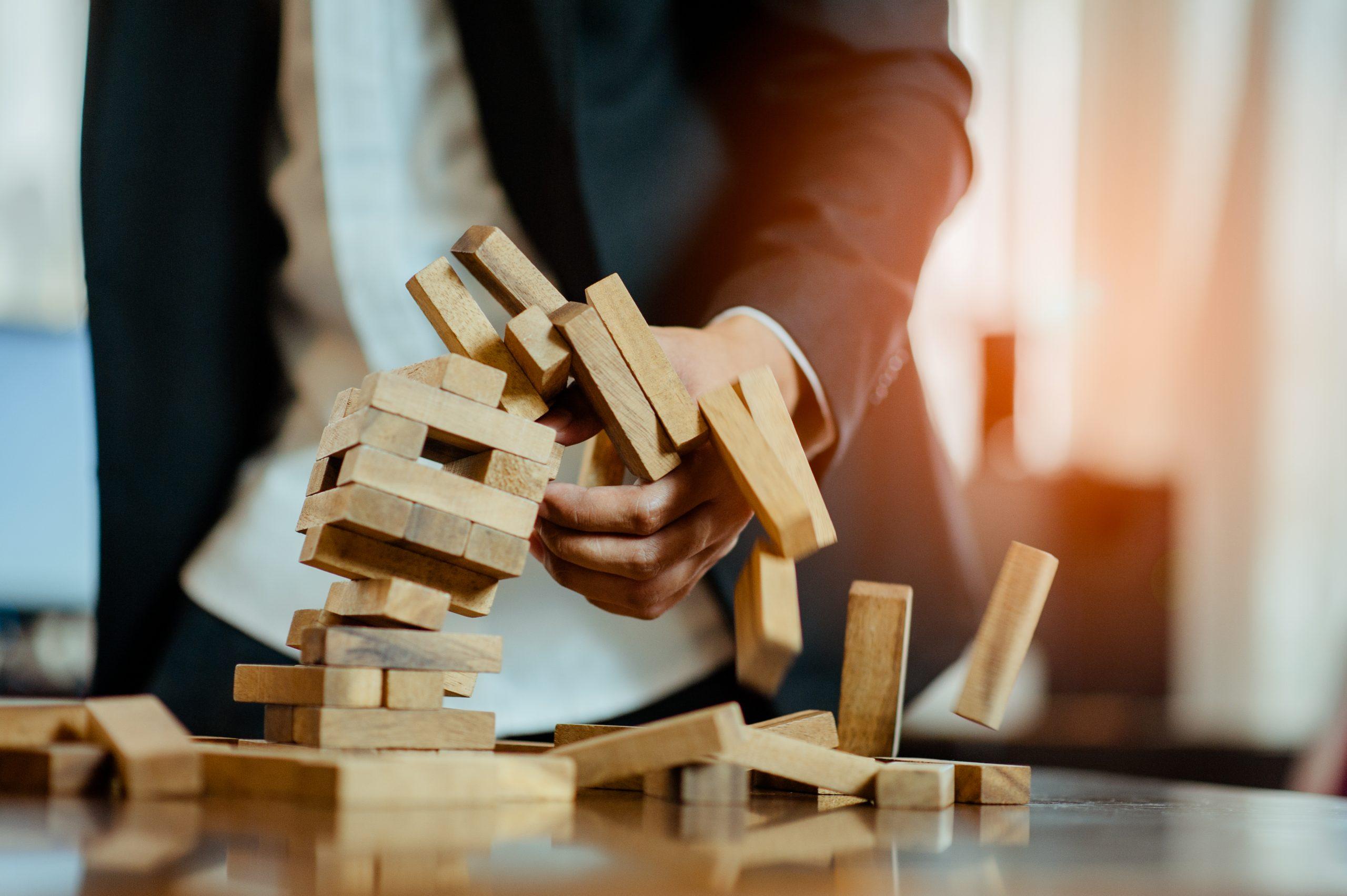 man breaking apart a tower of wooden blocks