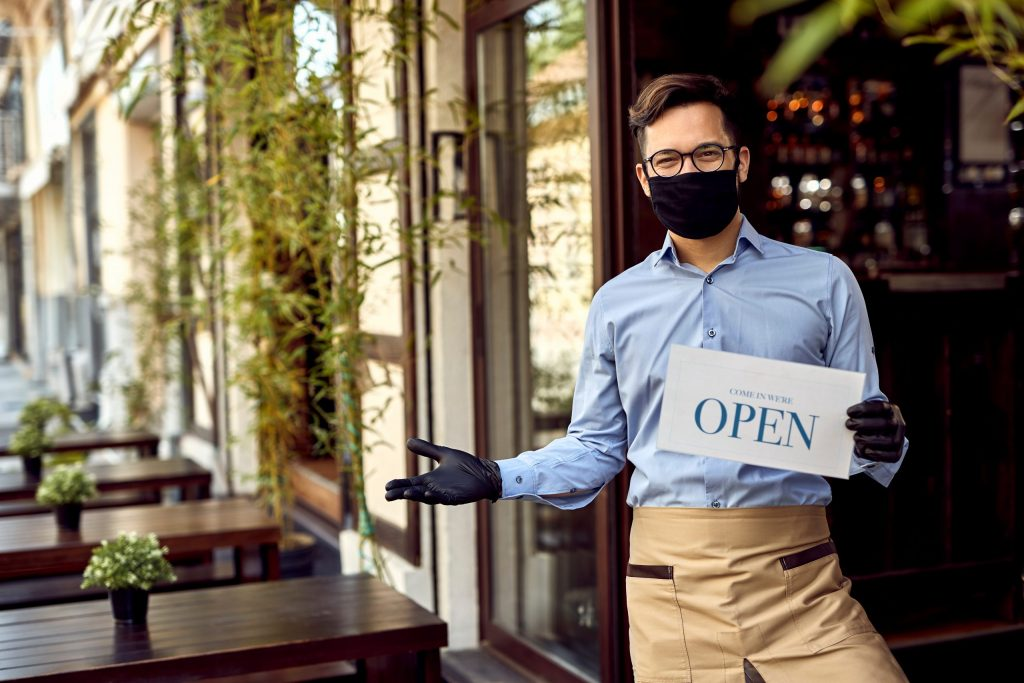 waiter wearing a mask welcomes customers to a restaurant