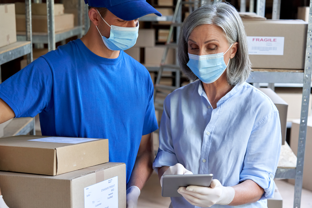 Female warehouse supervisor checks inventory with a male co-worker using a tablet