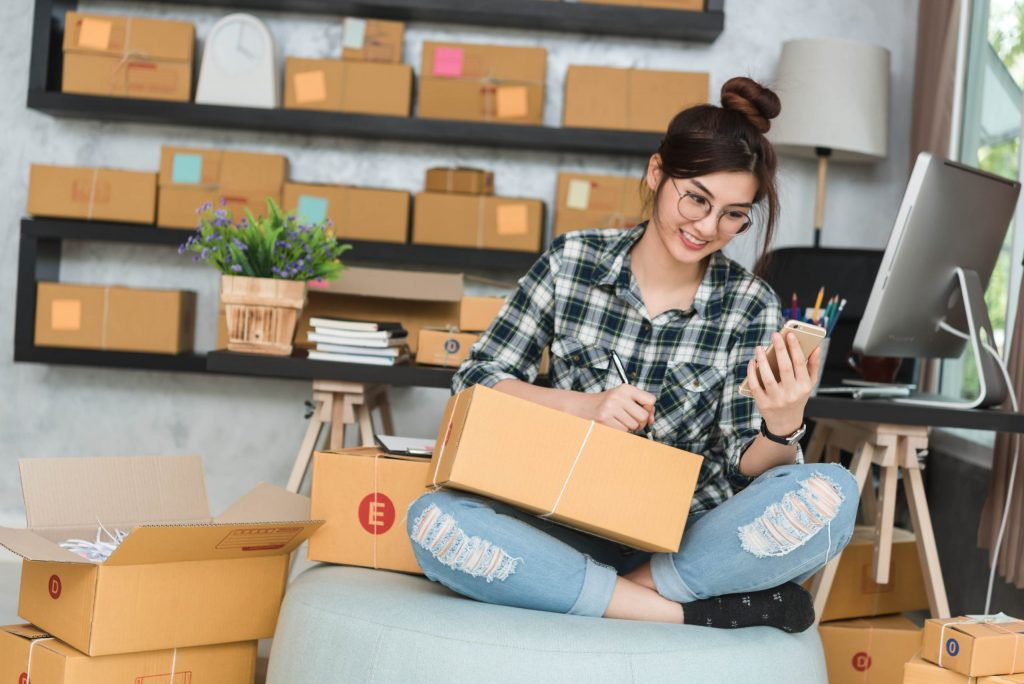 Businesswoman smiling as she packs orders and checks her phone